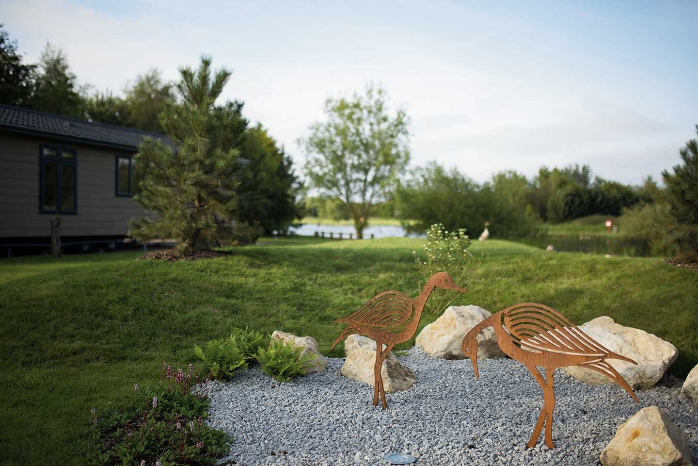 Two metal bird sculptures positioned in a landscaped area at The Lakes at Far Grange