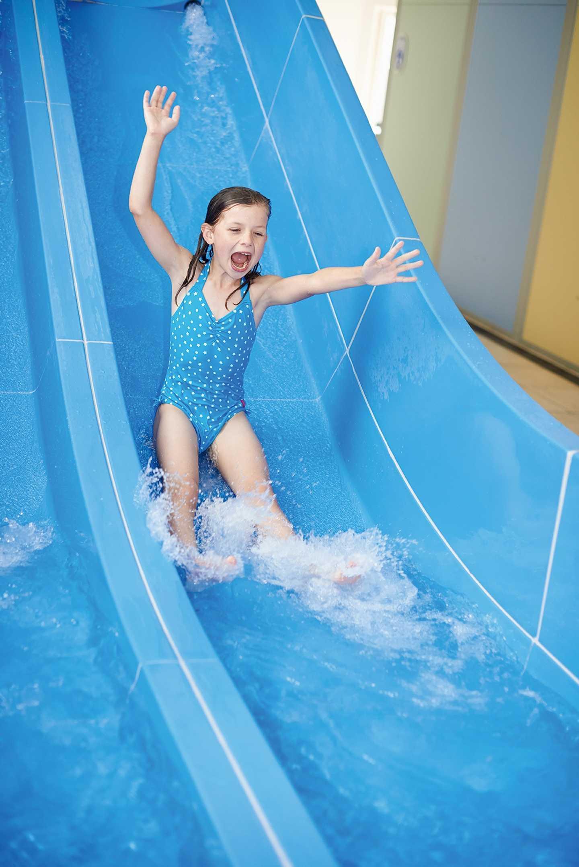 Girl whooshing down the indoor water slide