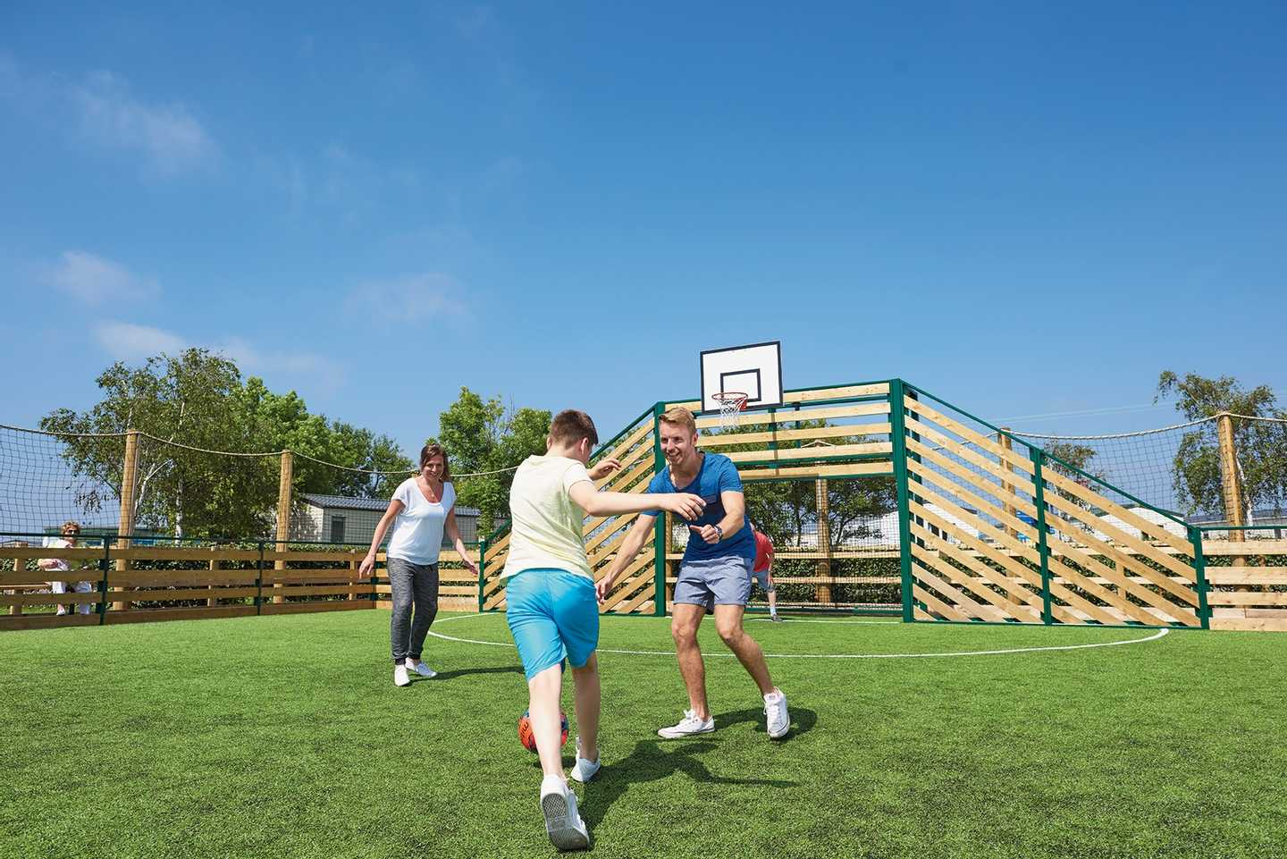 Family playing football on the all weather multi-sports court
