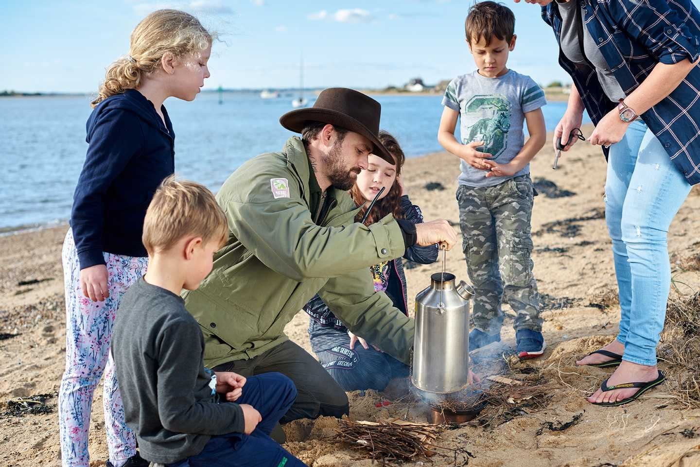 Family on the beach with a Ranger, heating a can of water over the fire they made at our Nature Rocks beach craft activity