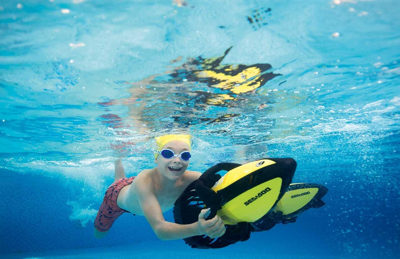Child holding onto submersible playing Aqua Jets
