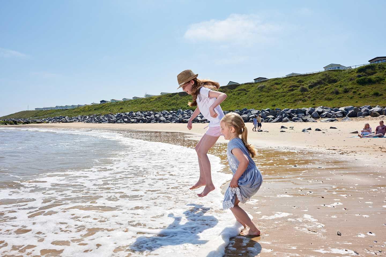 Girls jumping the waves at Hopton