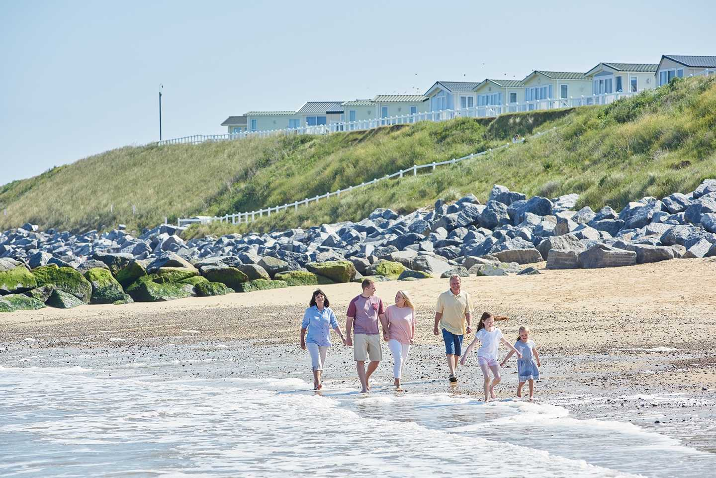A family strolling along the sandy Norfolk beach as the sea laps at their feet. Caravans are overlooking them at the top of the dunes.