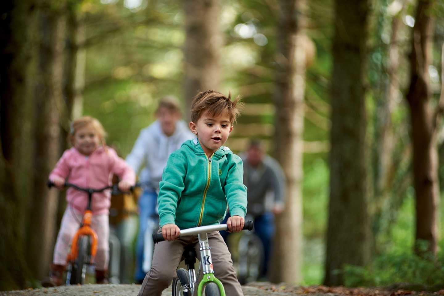A family having a bike ride through the woods