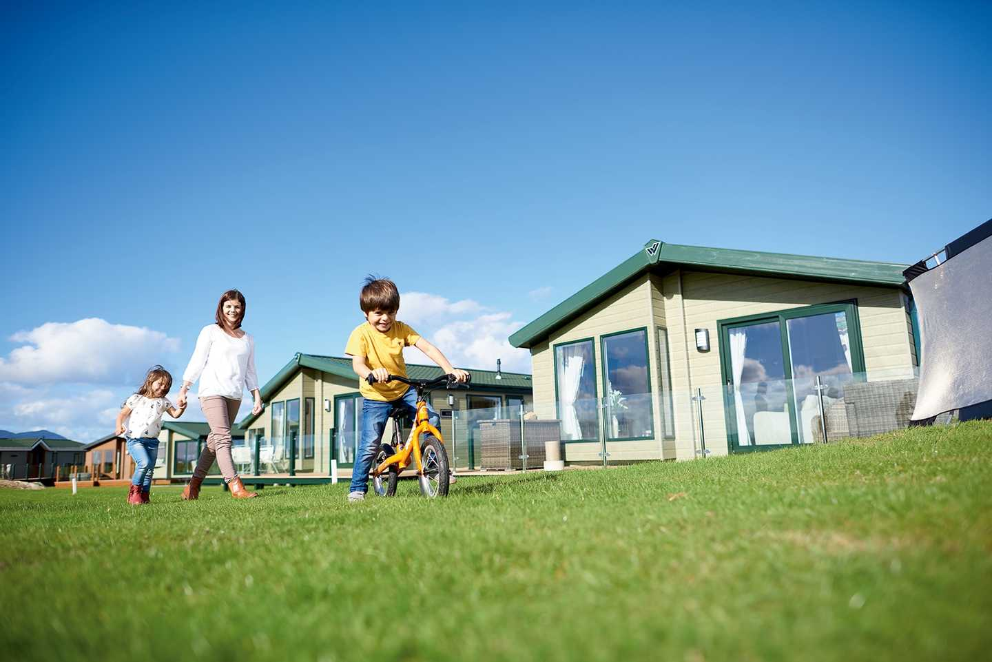 A family walking across the wide area of grass around our Golf Village area of Hafan y Môr Holiday Park with the young boy on his bike