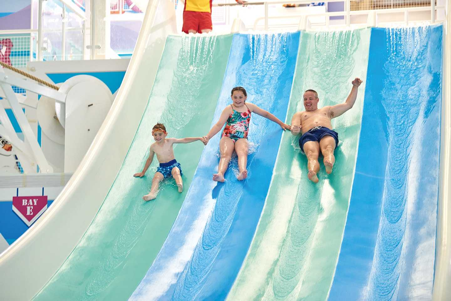 Family whizzing down the water flume in the heated indoor pool