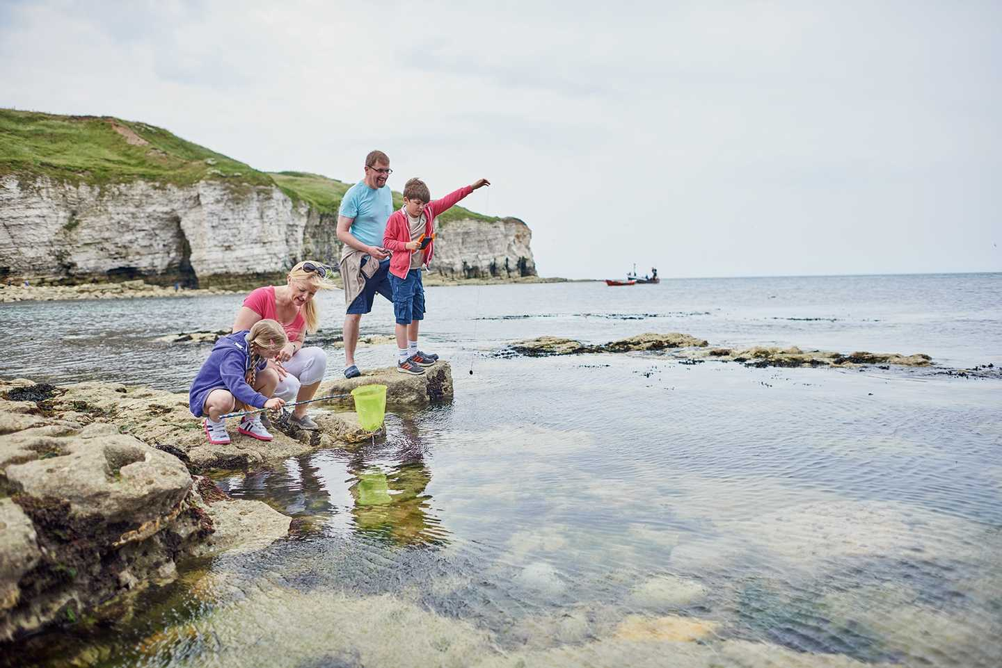Guests rock pooling at the beach