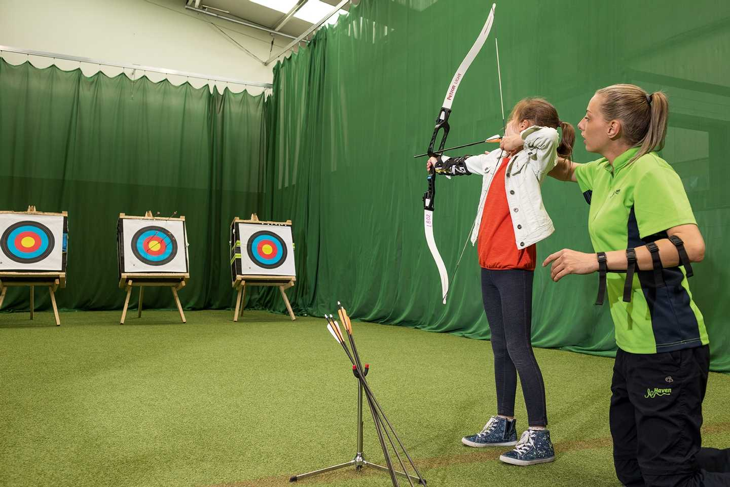 Child playing archery in the indoor activity barn