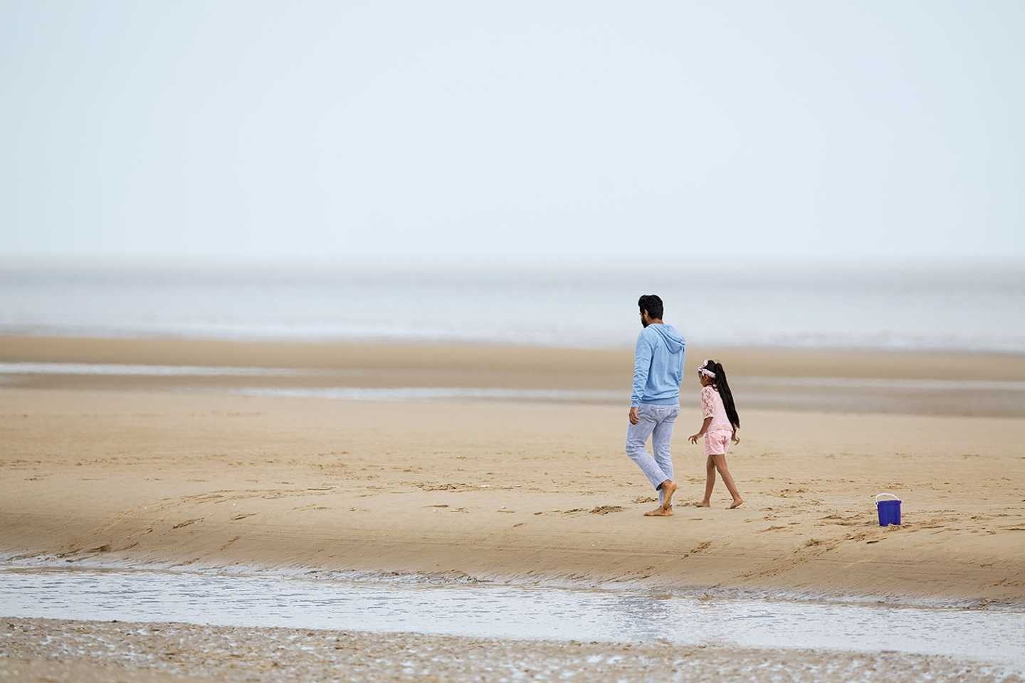 Dad walking with his Daughter along the beach