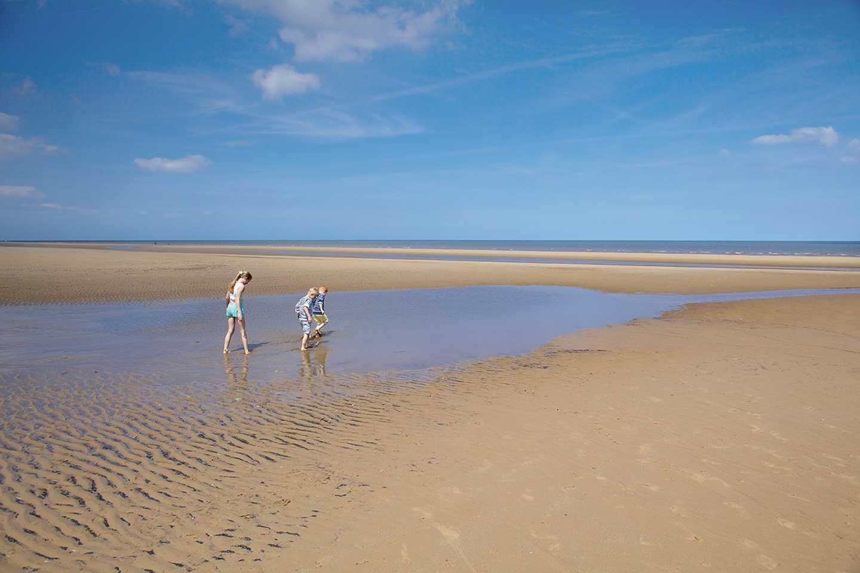 Children walking along the sand