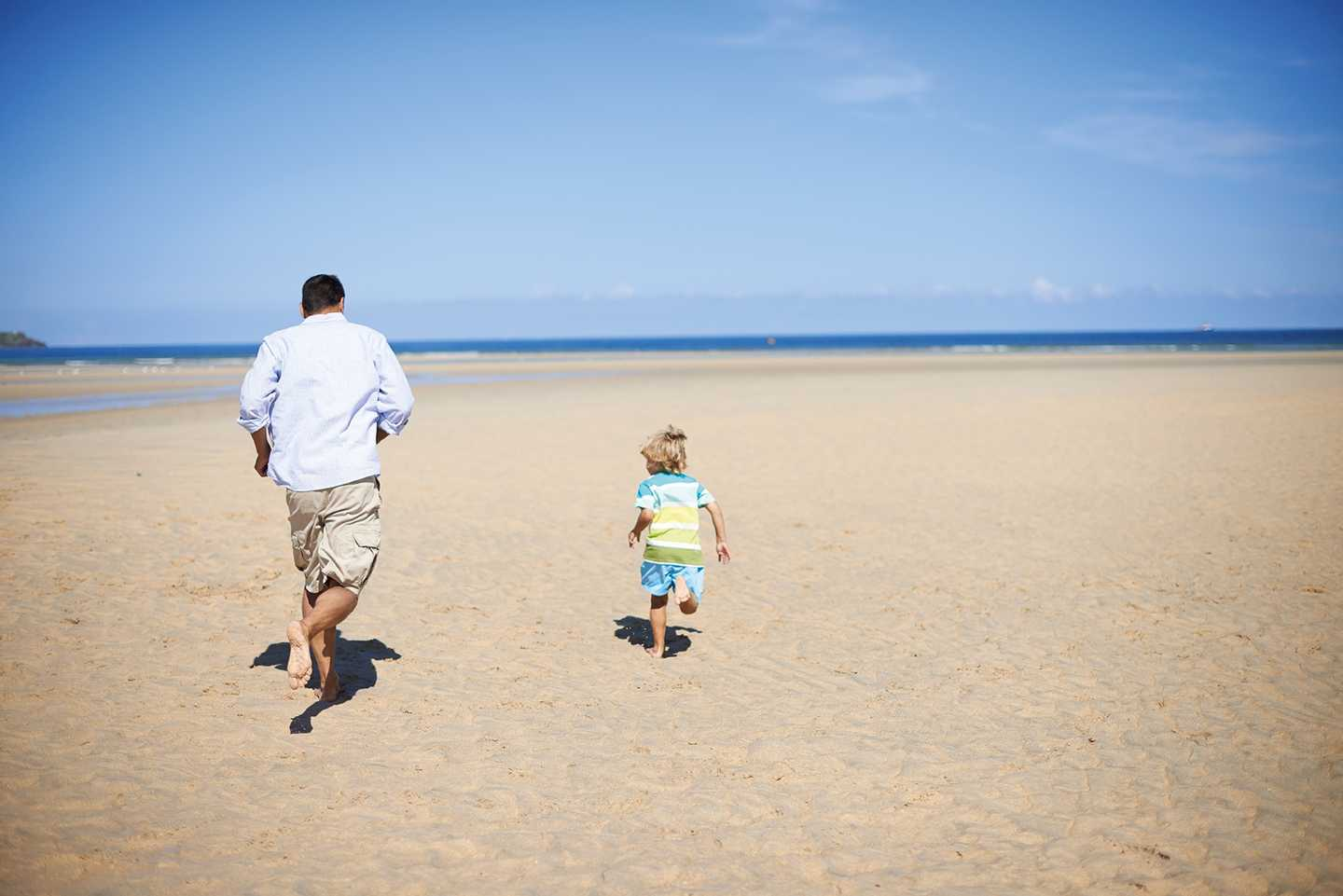 Dad and boy running on the beach