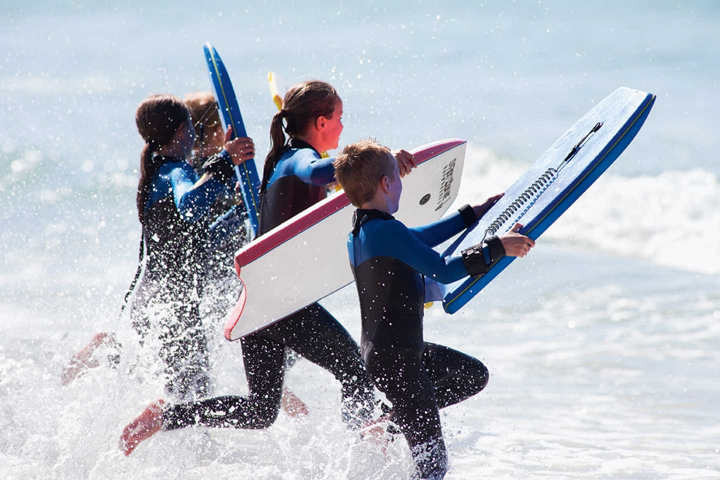 Children taking surfing and paddleboarding lessons