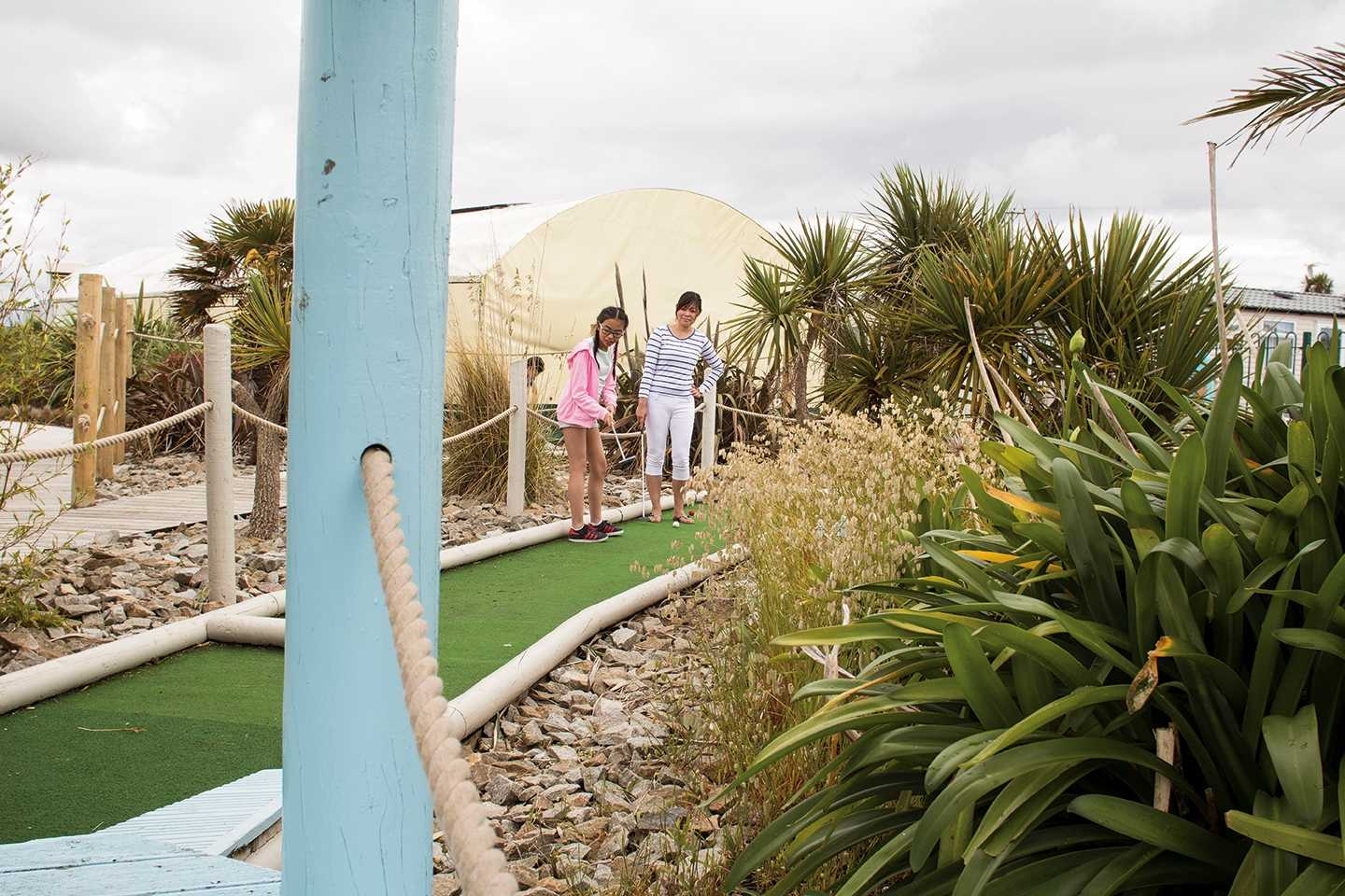 A family playing golf on the crazy golf course