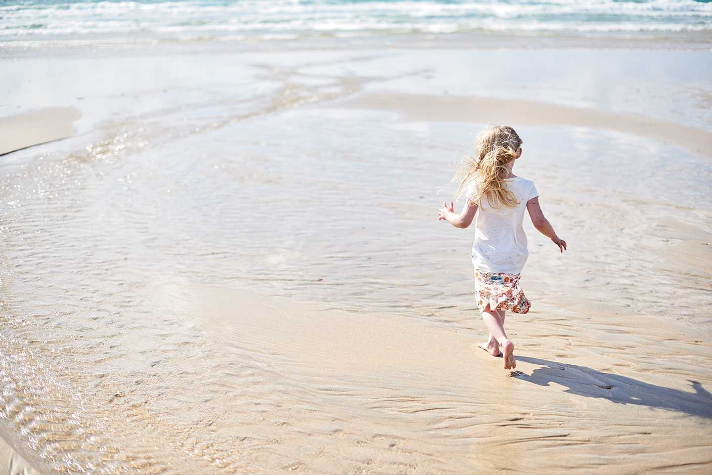 Little girl running on the sand