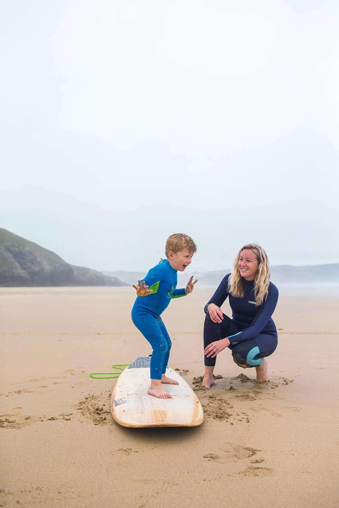 Boy balancing on a surfboard on sand