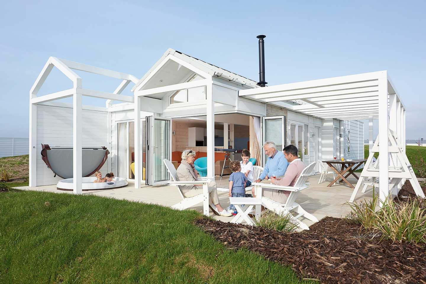 A family relaxing outside a Beach House on the decking and two women in the hot tub