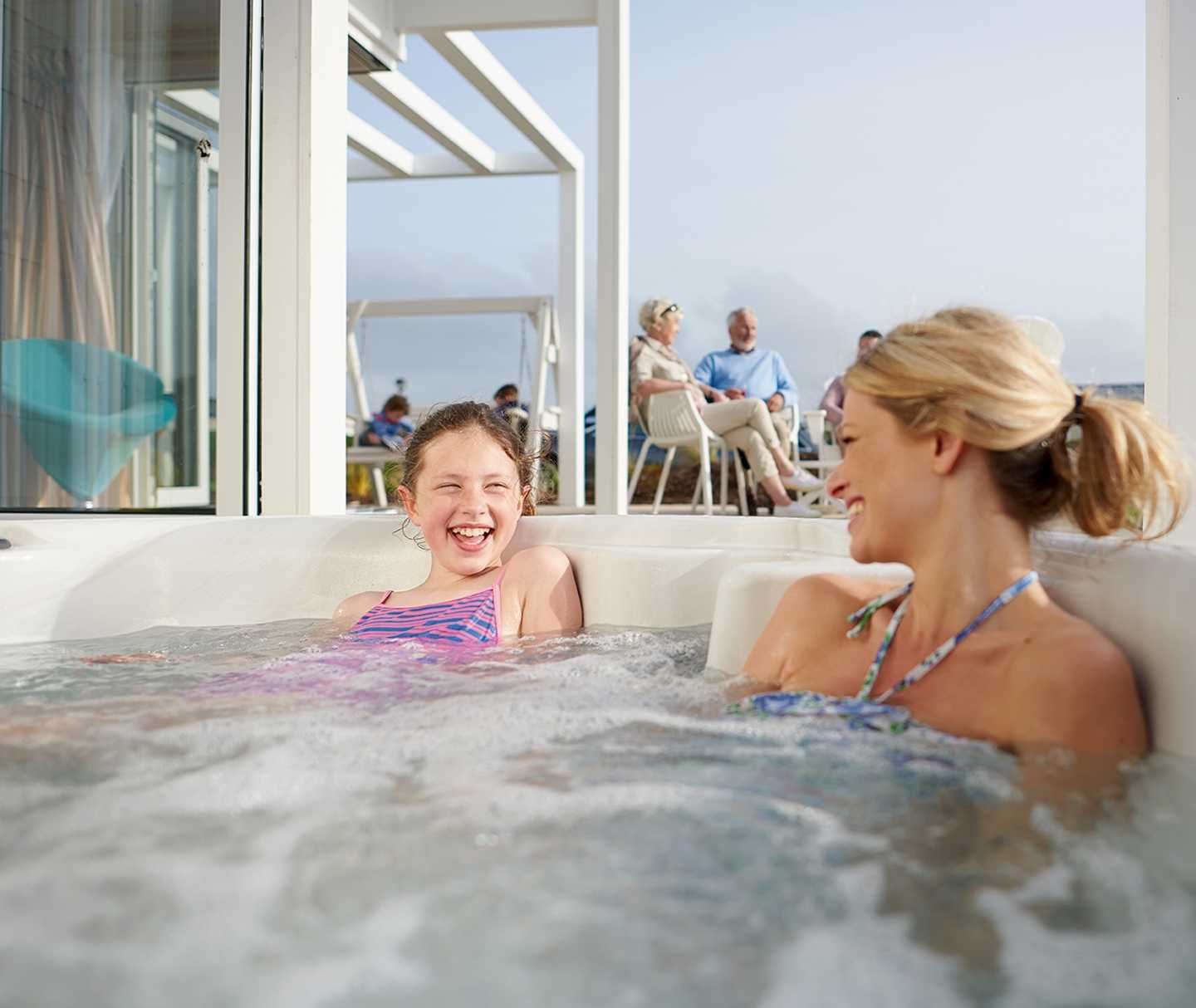 Two guests relaxing in the Beach House hot tub