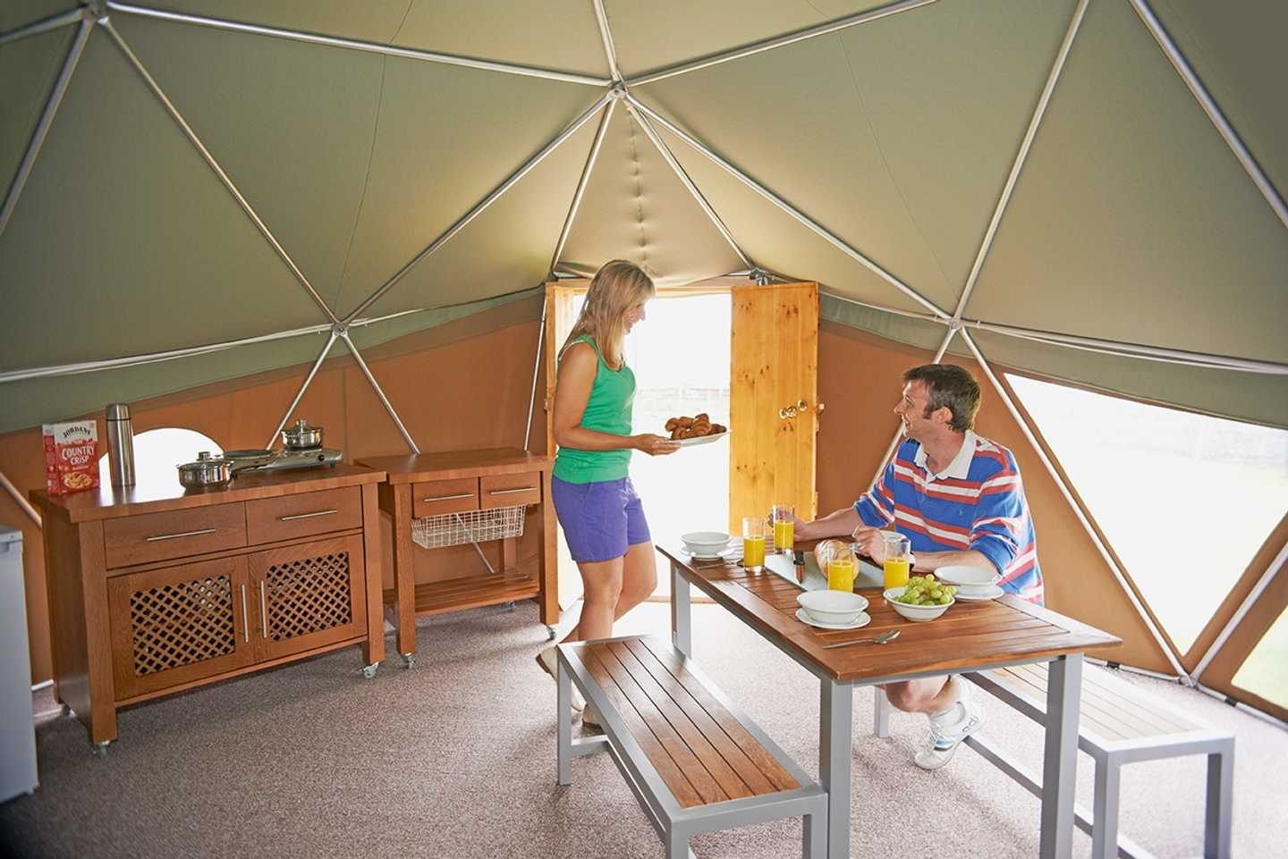 A couple eating breakfast at the table in a Geo Dome