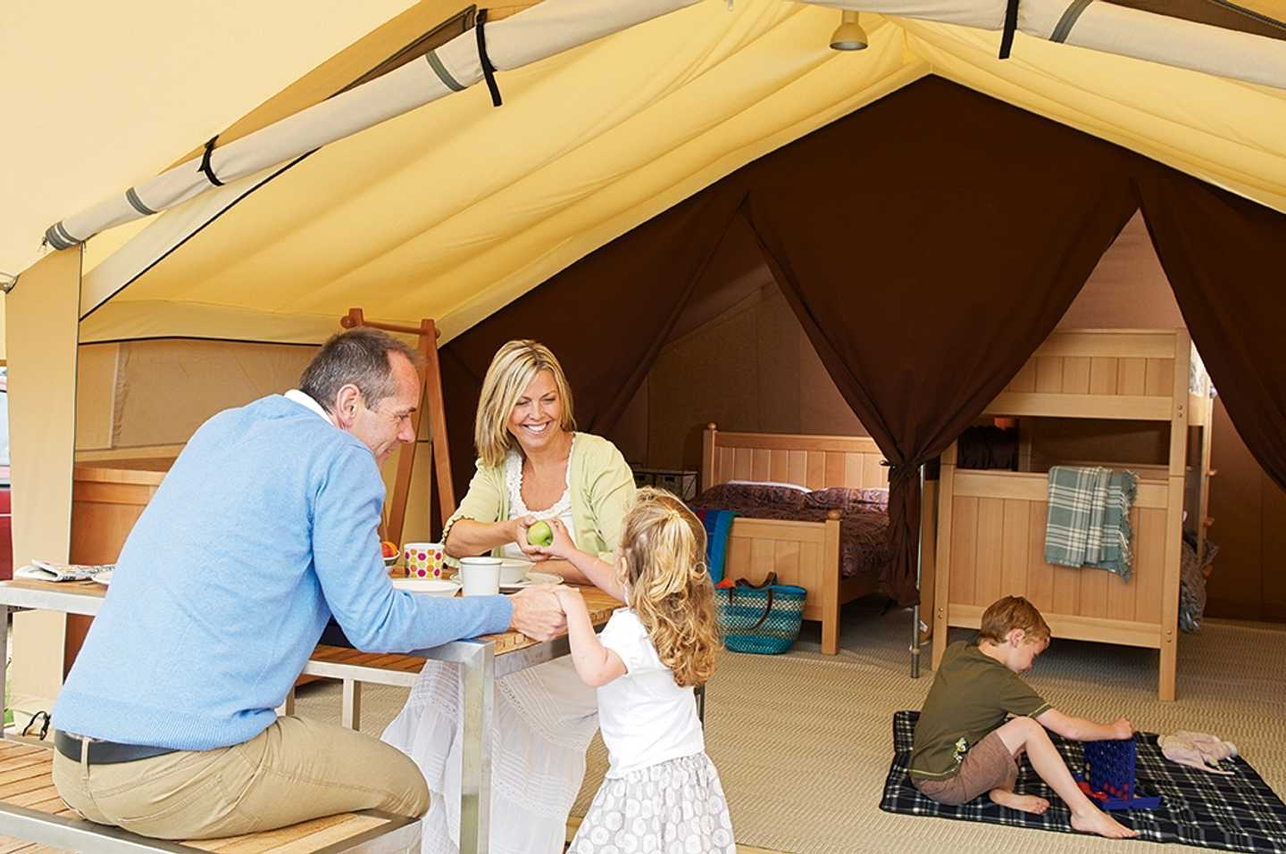 A family eating breakfast and playing in a Safari Tent