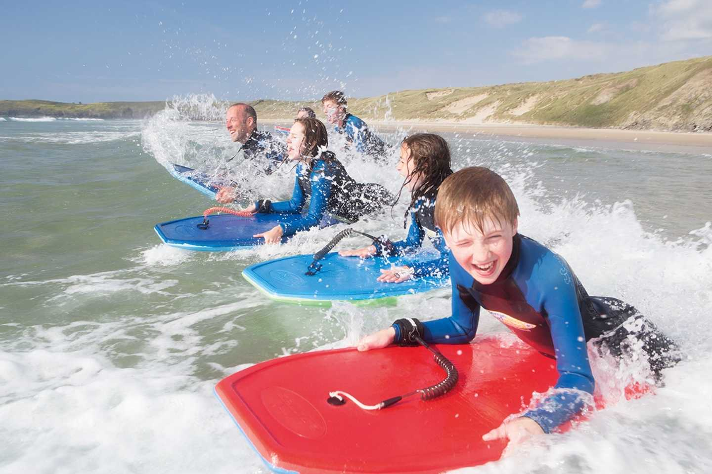 Guests surfing in the sea in Cornwall