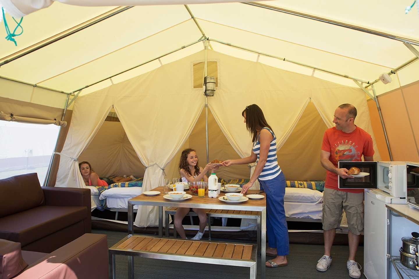 A family sitting down to eat breakfast in a Supertent