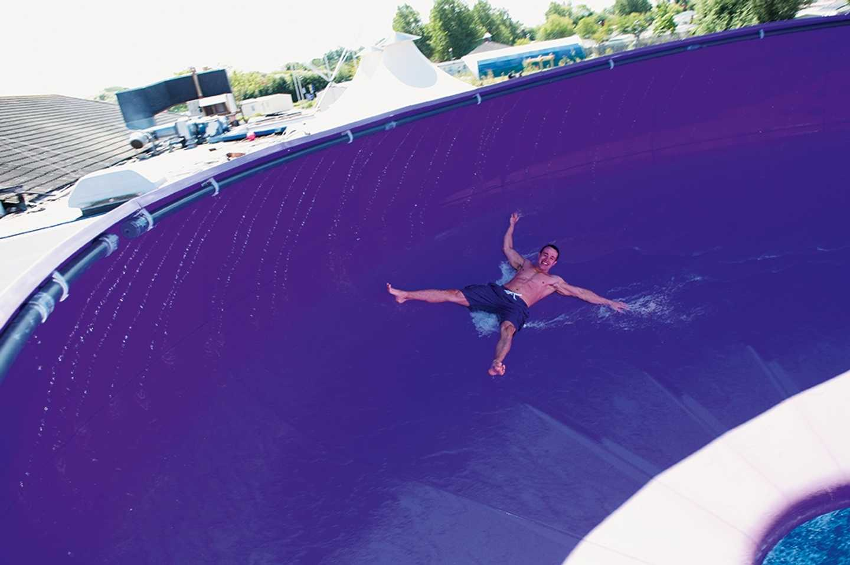 A boy sliding down the Space Bowl flume