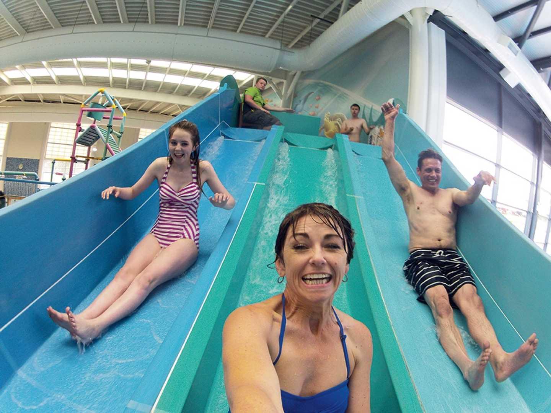 Children sliding down the indoor pool slide