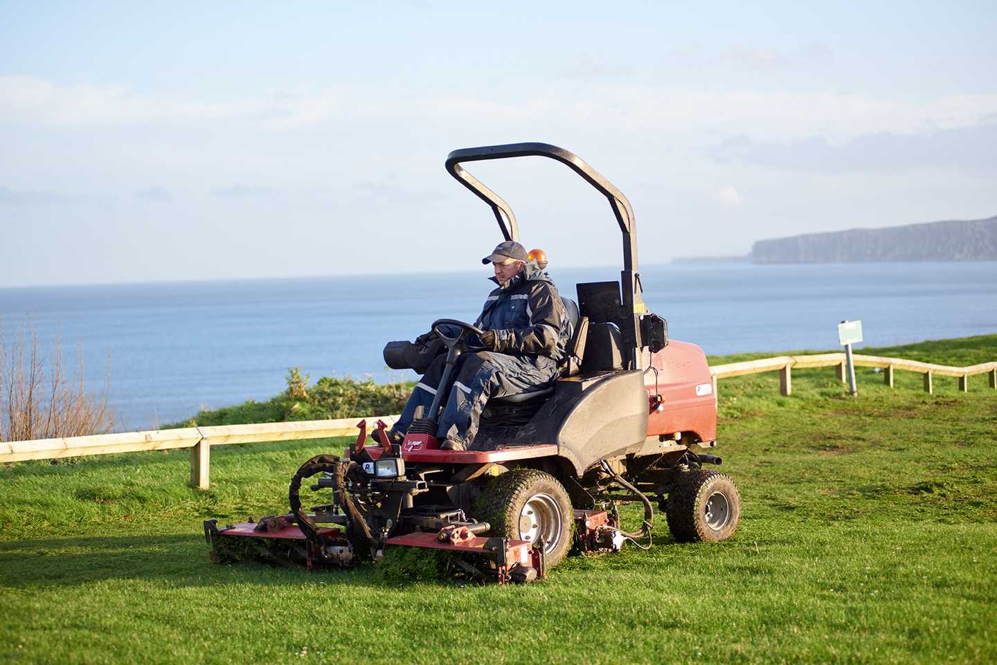A maintenance main mowing the grass
