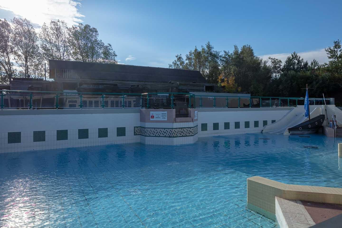 Guests having a swim and a drink by the outdoor pool