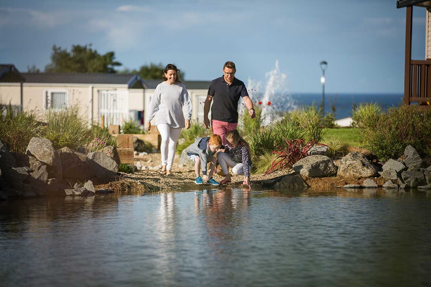 A family dipping their hands in one of the lakes at Primrose Valley, there's caravans and a fountain in the background