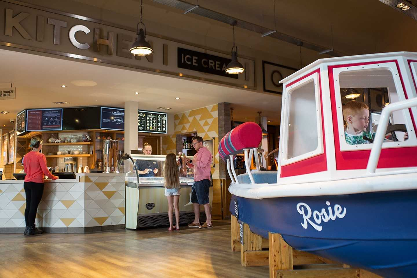 Guests getting ice-cream at The Lakehouse Kitchen and a boy in the boat in The Lakehouse restaurant