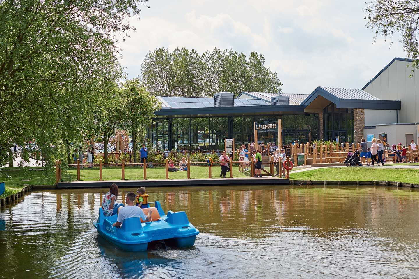 Guests in a pedalo on the boating lake overlooking The Lakehouse restaurant