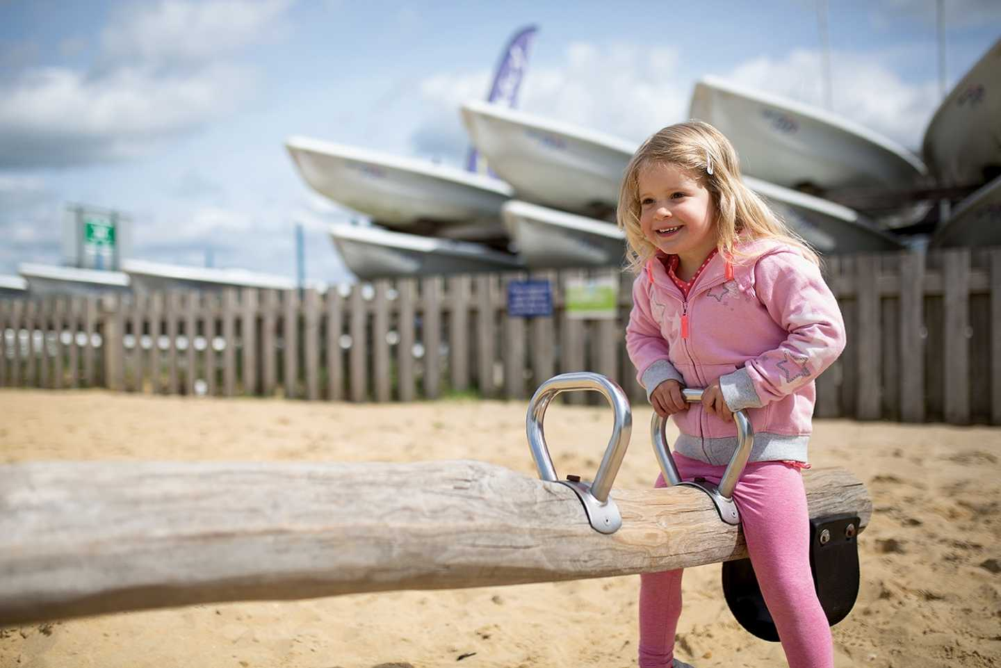 Children enjoying the wooden seesaw at the outdoor play area on the beach