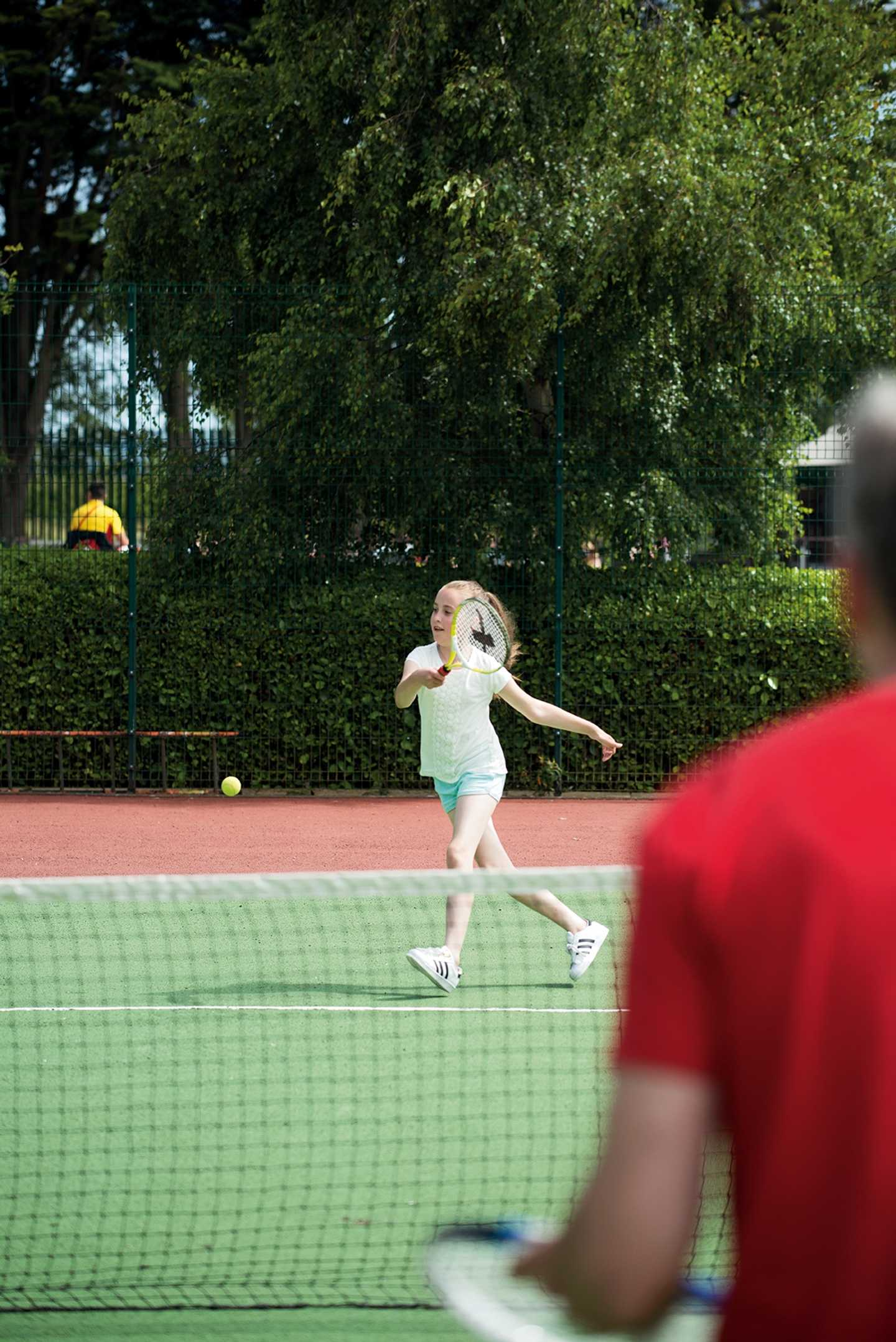A father and daughter playing tennis