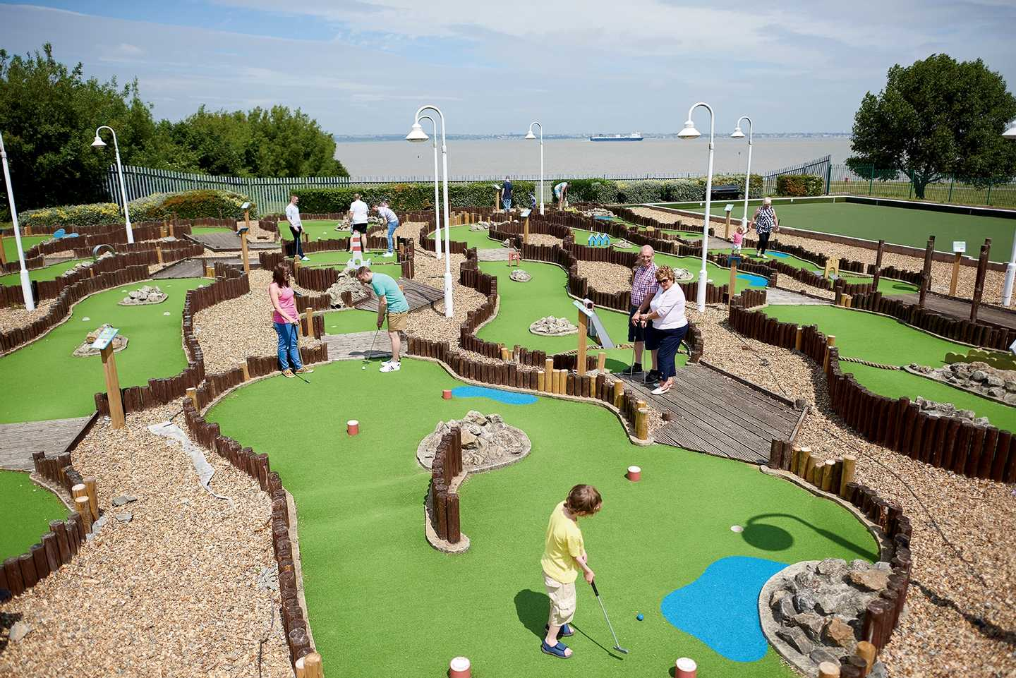 Family playing on the crazy golf course at Allhallows