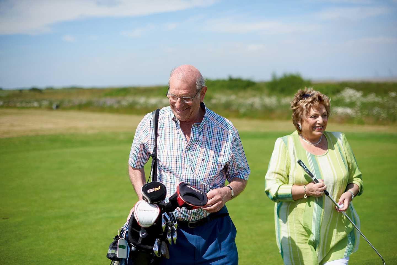 A couple walking along the 9-hole golf course