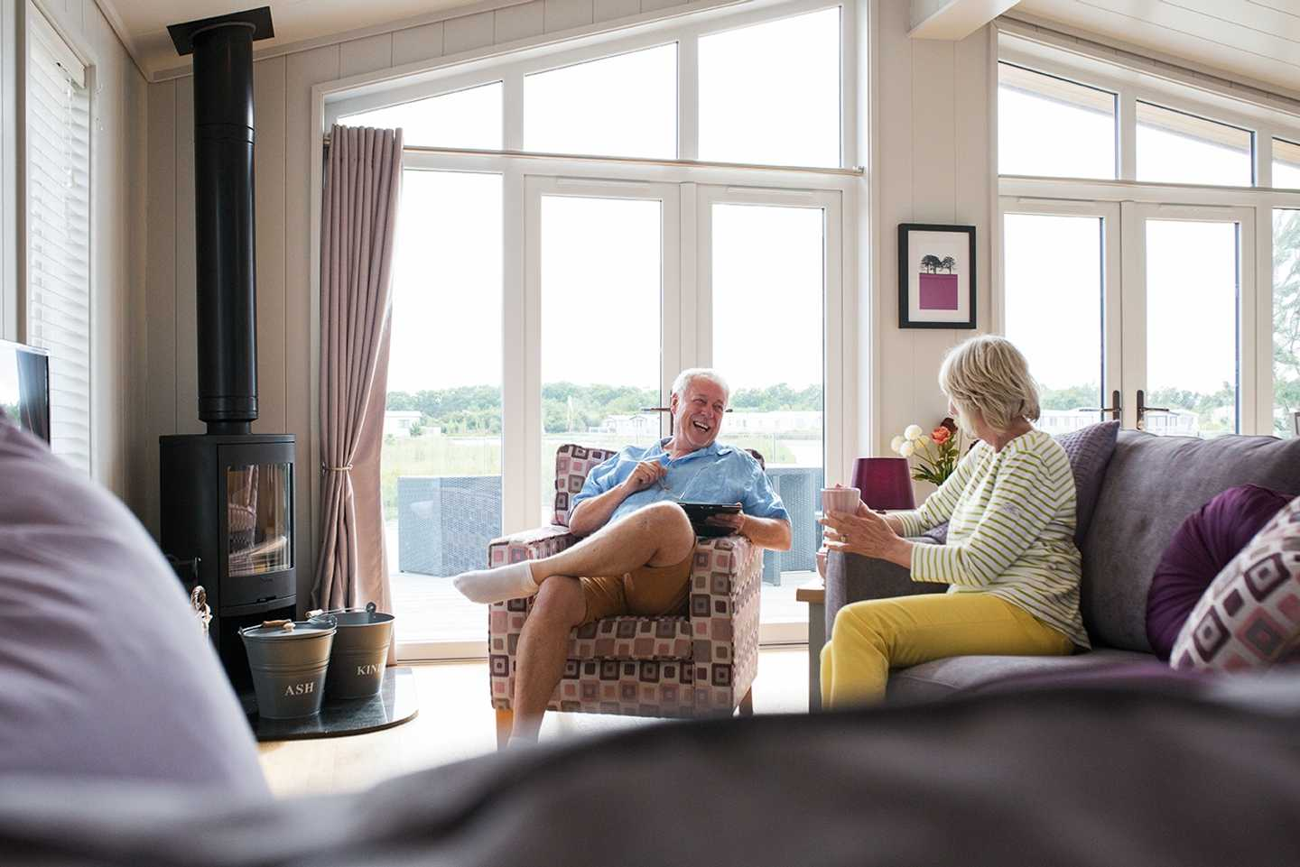 A couple laughing as they enjoy a cuppa inside their lodge with a log burner in the corner
