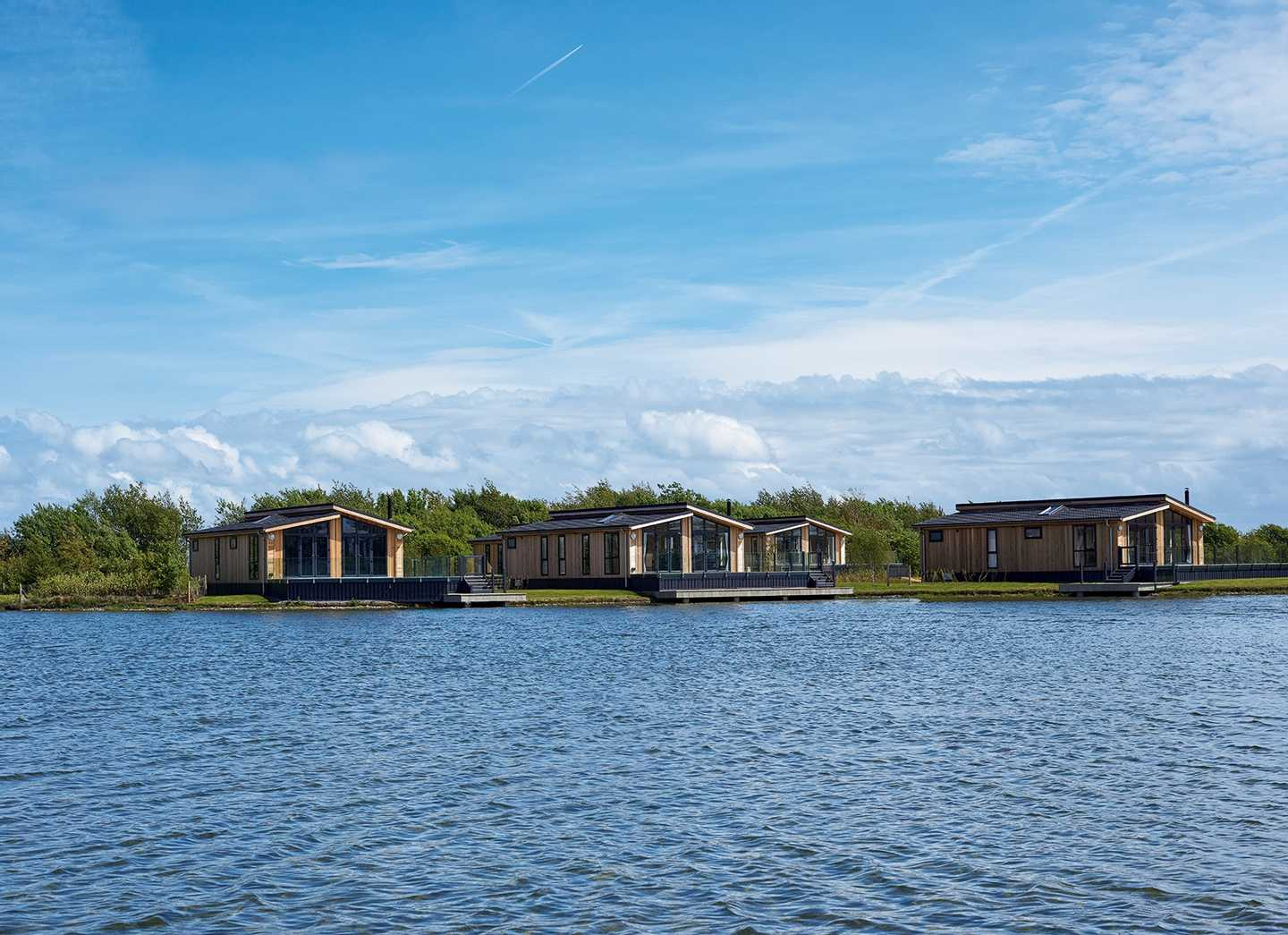 4 of our lodges at Tarka Holt perched on the large lake