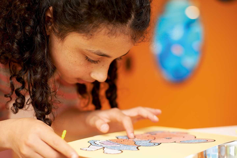 Girl enjoying creating sand art
