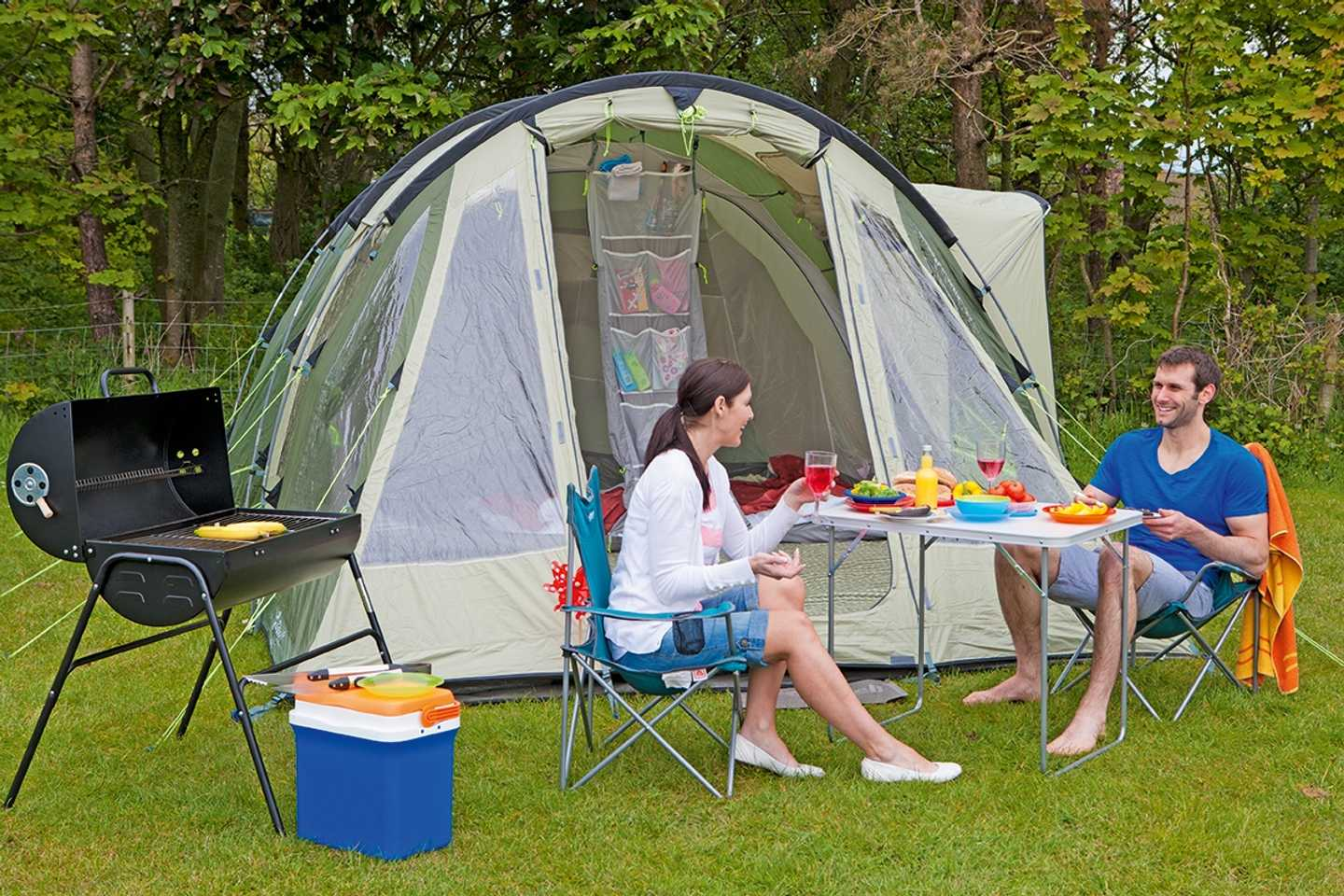 Guests outside their tent with awning