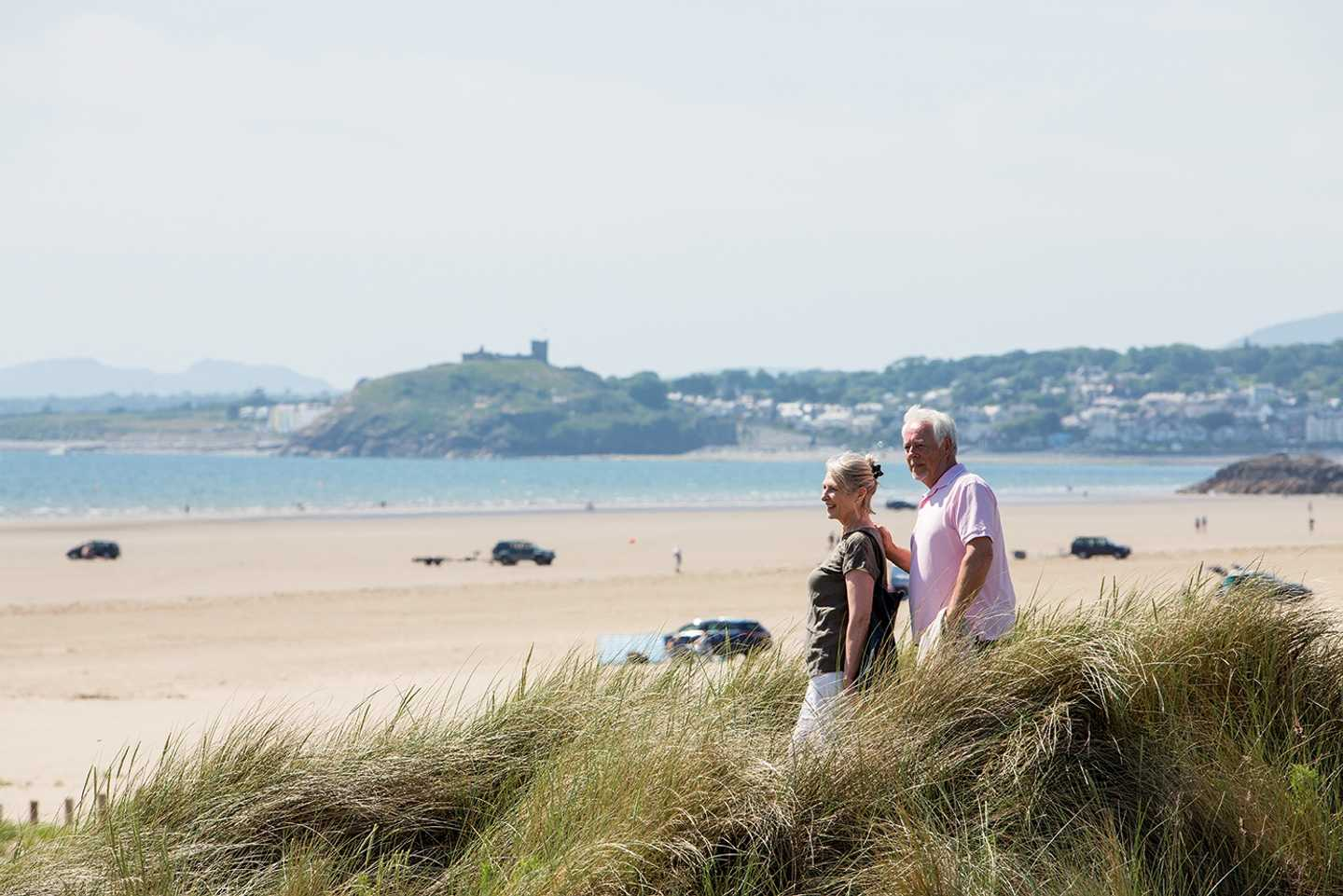 A couple looking across the vast stretch of the golden, sandy beach at Greenacres Holiday Park with the sea and an old castle in the background