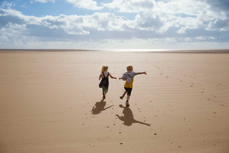 Children running along a beach