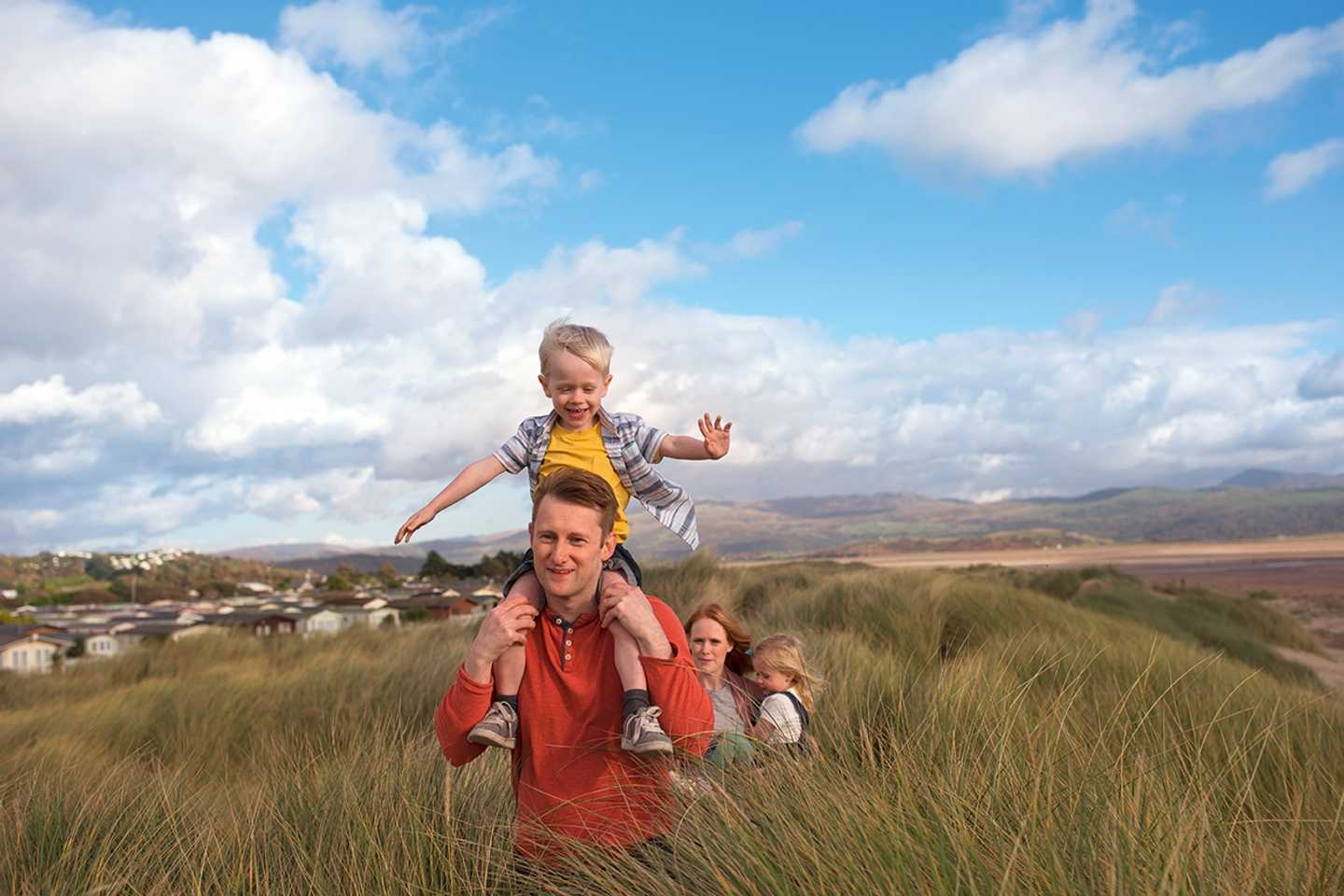 Boy having a piggy back from his Dad across the Dunes at Greenacres