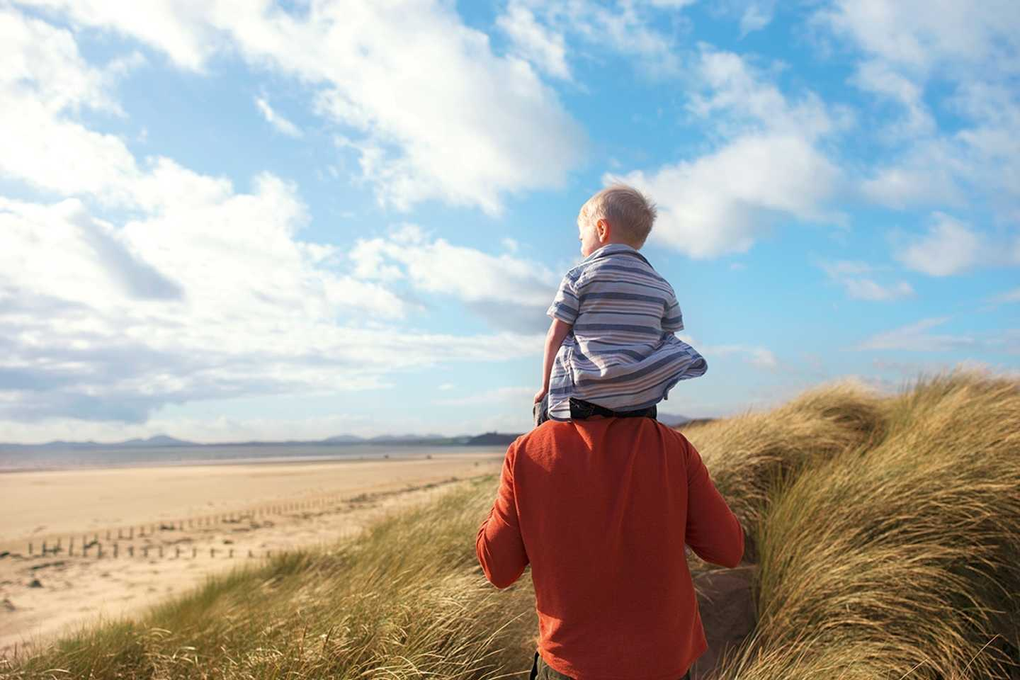 Father and child looking out over the beach