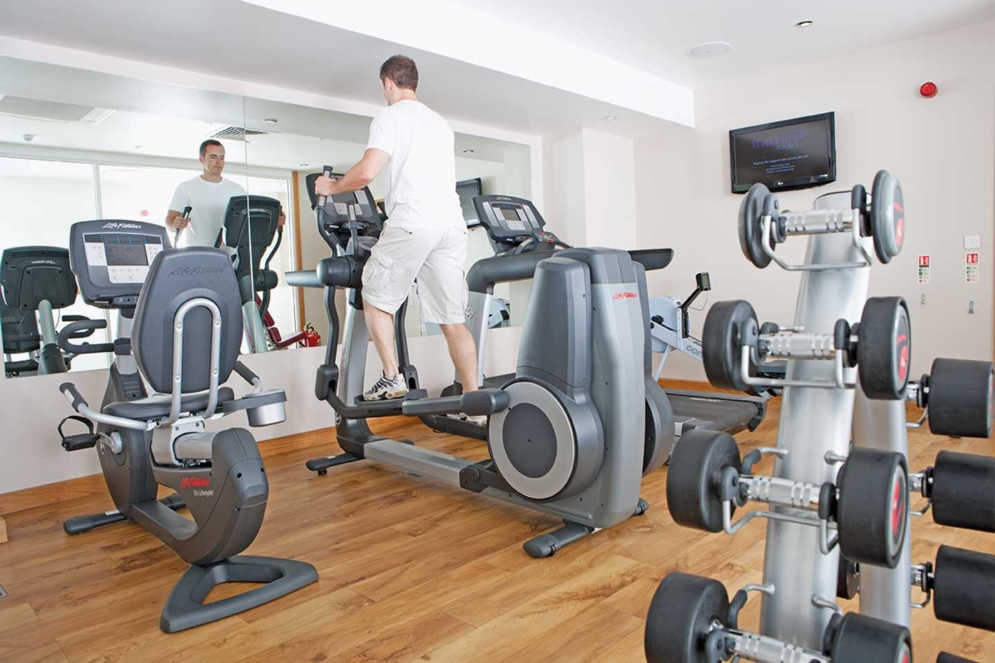 A man working out on the cross-trainer in our owners' gym