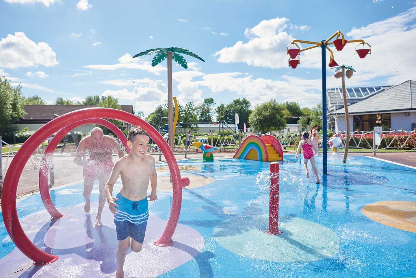 A boy and his father splashing through the outdoor SplashZone