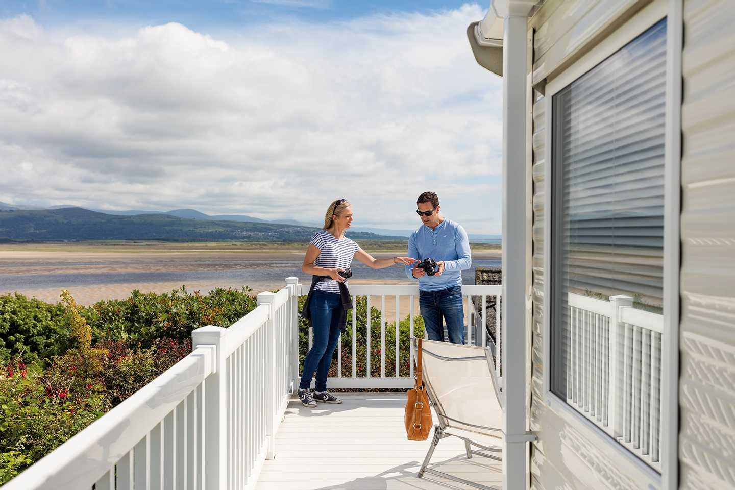 Owners standing on the veranda of their holiday home