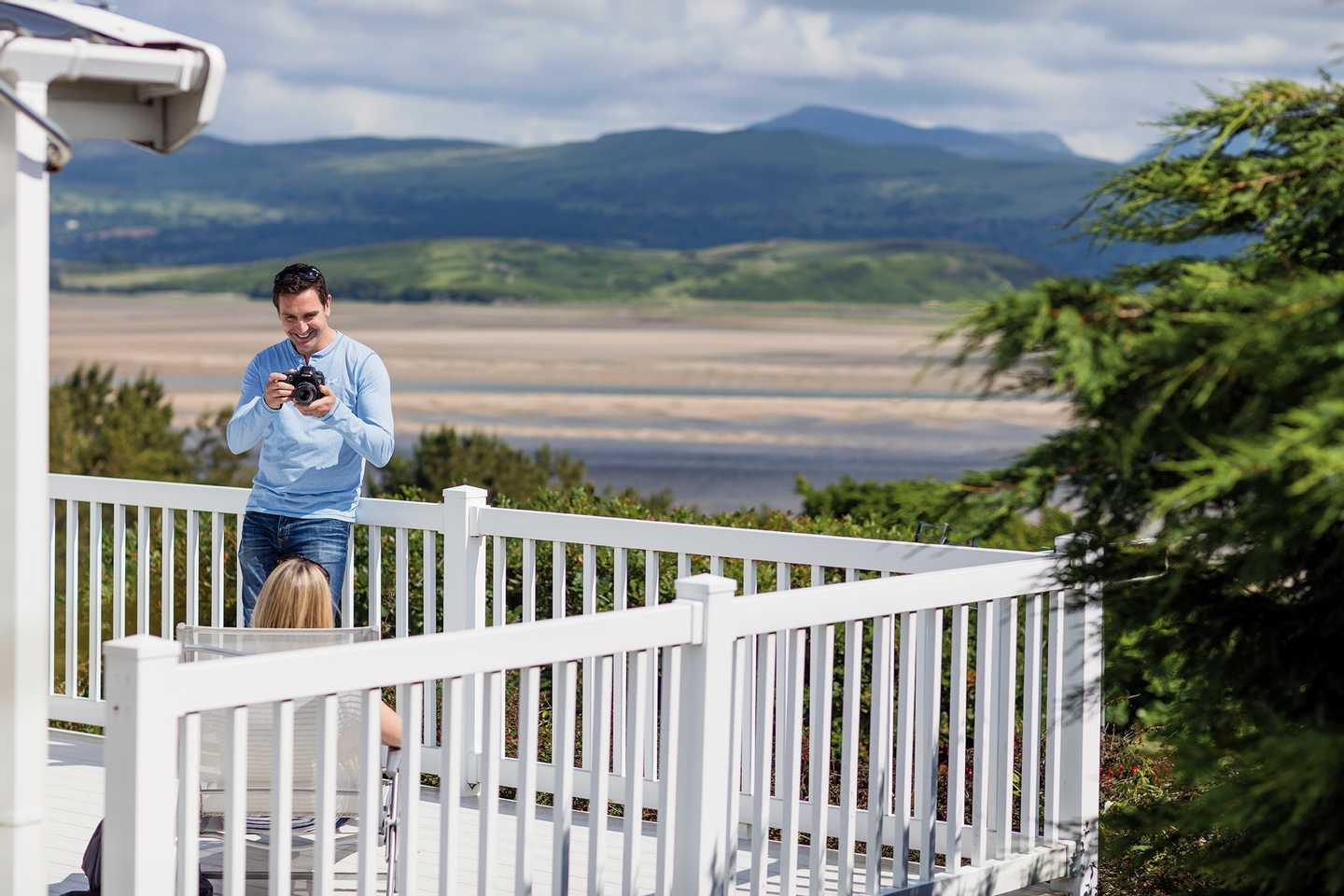 An owner standing on his veranda of his holiday home at Garreg Wen