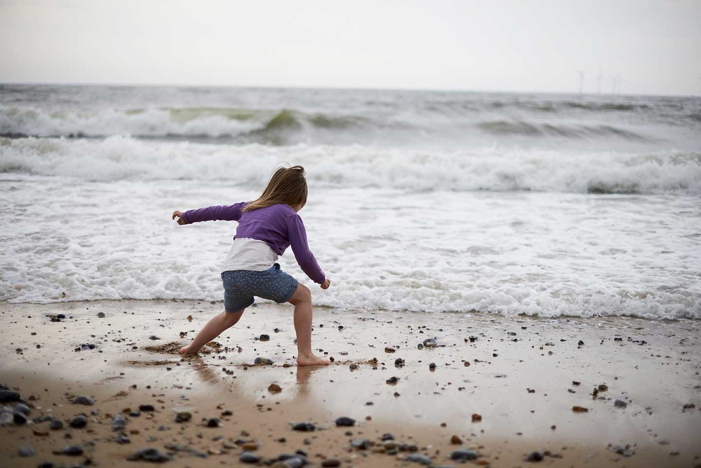 Child burying her toes in the sand by the waters edge on the beach