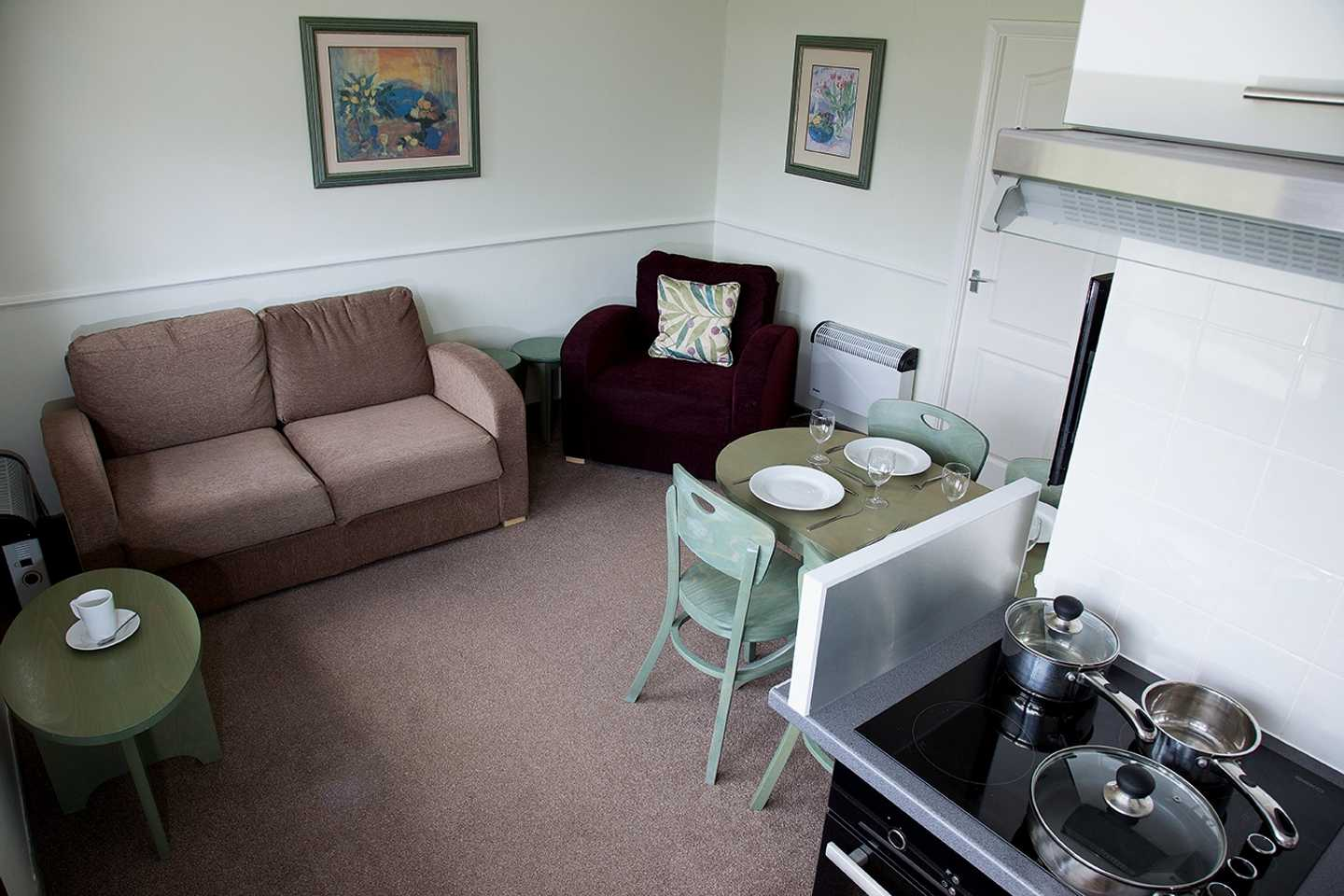 A Standard chalet lounge with a sofa, dining table and cooker